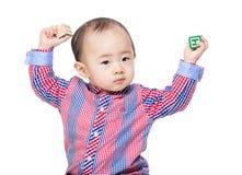 Azja chłopiec chwyta zabawki dwa i blok wręczamy up Fotografia Stock