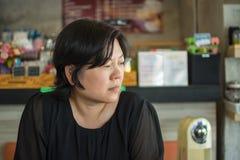 Azja kobiet myśl w sklep z kawą Obraz Stock