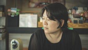 Azja kobiet myśl w sklep z kawą Zdjęcie Royalty Free