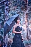 Azja kobieta w czerni długiej sukni z umbella pozycją na lesie Zdjęcie Stock