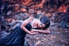 Azja kobieta w czerni długim smokingowym lying on the beach na kamieniu Zdjęcie Royalty Free