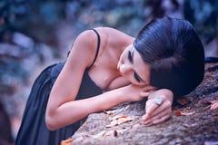 Azja kobieta w czerni długim smokingowym lying on the beach na kamieniu Obrazy Royalty Free