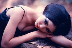 Azja kobieta w czerni długim smokingowym lying on the beach na kamieniu Obraz Royalty Free