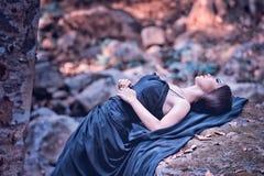 Azja kobieta w czerni długim smokingowym lying on the beach na kamieniu Zdjęcia Royalty Free