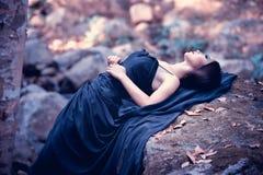 Azja kobieta w czerni długim smokingowym lying on the beach na kamieniu Obrazy Stock