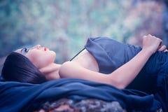Azja kobieta w czerni długim smokingowym lying on the beach na kamieniu Obraz Stock