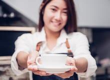 Azja kobiety barista odzieży cajgowy fartuch trzyma gorącą filiżankę słuzyć zdjęcia stock