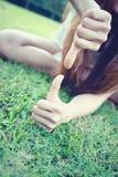 Azja kobiety kłama z ręką pokazuje kciuk w górę i na dół zdjęcia stock