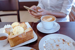 Azja kobiety które piją kawę i patrzeją jego telefon komórkowego przy sa Zdjęcia Stock