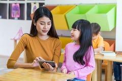Azja kobiety nauczyciel uczy dziewczyna ucznia z pastylka komputerem w cl Fotografia Stock