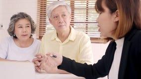 Azja mądrze żeński agent oferuje ubezpieczenie zdrowotne dla starszych par dokumentem, pastylką i laptopem, Starzeję się Azjatyck zbiory wideo
