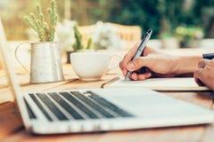 Azja mężczyzna ręki writing notatnika papier na drewno stole w kawowym sho Zdjęcia Stock