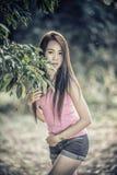 Azja młoda kobieta jest ubranym menchie przekazuje i krótcy cajgi Zdjęcia Stock
