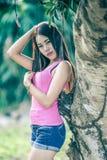 Azja młoda kobieta jest ubranym menchie przekazuje i krótcy cajgi Fotografia Stock