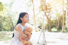 Azja mała dziewczynka z lala niedźwiedziem siedzi na huśtawce obrazy stock