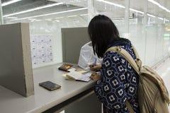 Azja podróżnika tajlandzkie kobiety pisze odjazd karcianej i przyjazdowej karcie przy kontuarem Obraz Royalty Free