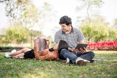 Azjata dobiera się czytać książkę Para ucznie z książki Edukacja w natura parku obraz stock