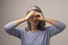 Azjata dojrzała kobieta ok gest jak lornetki obraz stock