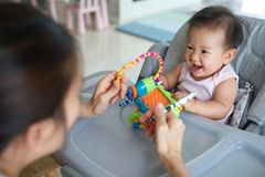 Azjata matka bawić się zabawkę z jej dziecka obsiadaniem na łomotania krześle obraz stock