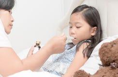 Azjata matka daje ona córka syropowi przez grypy zdjęcia stock