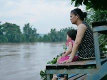 Azjata matka i jej mała córka jej stroną patrzeje mroczną błotnistą rzekę po opady deszczu zdjęcia royalty free
