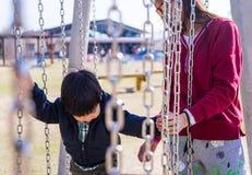 Azjata matka pomaga jej syna w boisku Zdjęcie Royalty Free