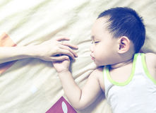 Azjata mienia dziecka macierzysta ręka podczas gdy śpiący Fotografia Royalty Free