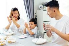 Azjata rodzice klascze ręki i daje komplementowi jako ich dziecko robią dobrej pracie podczas gdy mieć posiłek wpólnie w domu obraz stock