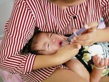Azjata ` s ręki macierzysty opakowanie wokoło jej płacz dziewczynki ` s twarzy zmusza dziecka brać ciekłą medycynę Zdjęcia Royalty Free