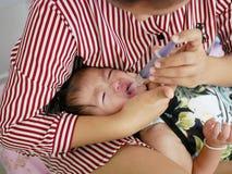 Azjata ` s ręki macierzysty opakowanie wokoło jej płacz dziewczynki ` s twarzy zmusza dziecka brać ciekłą medycynę Zdjęcie Royalty Free