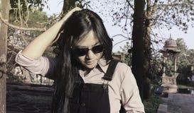 Azjaty czarni włosy długie kobiety jest ubranym okulary przeciwsłonecznych, jest ubranym czarnych kombinezonów cajgi stoi w plene zdjęcie royalty free