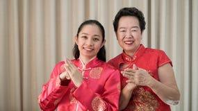 Azjaty daugther w prawie w Chiense czerwonym kostiumu dla nowego roku i matka zdjęcia stock
