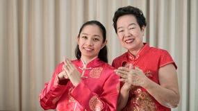 Azjaty daugther w prawie w Chiense czerwonym kostiumu dla nowego roku i matka obraz royalty free