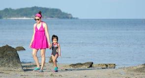 Azjaty Macierzysty i żeński berbecia dziecko podczas gdy chodzący w miejscowości nadmorskiej obrazy stock
