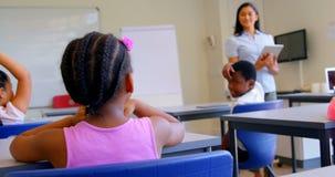Azjatyccy żeńskiego nauczyciela nauczania schoolkids w sali lekcyjnej przy szkołą 4k zdjęcie wideo
