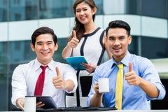 Azjatyccy biznesmeni pracuje outside z kawą obraz stock