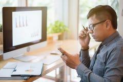 Azjatyccy biznesmeni używają smartphones przy biurowym biurkiem poj?cia prowadzenia domu posiadanie klucza z?oty si?gaj?cy niebo fotografia royalty free