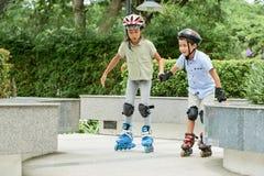 Azjatyccy dzieci jedzie rolkowe łyżwy w parku zdjęcie stock