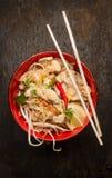 Azjatyccy kluski z chopstick, kurczakiem i flancami na ciemnym drewnianym tle, obraz stock
