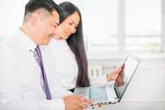 Azjatyccy ludzie biznesu analizują pracę na laptopie przy biurem obrazy stock