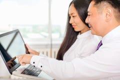 Azjatyccy ludzie biznesu analizują pracę na laptopie przy biurem zdjęcie royalty free