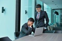 Azjatyccy ludzie biznesu ma kłopotu działanie, wini przy biurem zdjęcia royalty free