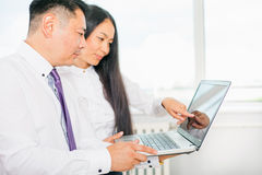 Azjatyccy ludzie biznesu używa laptop przy biurem fotografia royalty free