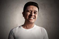 Azjatyccy mężczyzna mruga i szczęśliwy wyrażenie obrazy stock