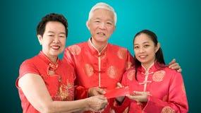 Azjatyccy rodzice dają czerwieni odkrywają córka chińczyka nowy rok obrazy royalty free