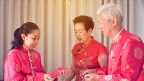 Azjatyccy rodzice daj? czerwieni odkrywaj? c?rka chi?czyka nowy rok zdjęcia royalty free