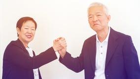 Azjatyccy starsi ludzie biznesu pary mienia ręki dla pomyślnego Zdjęcie Royalty Free