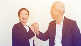 Azjatyccy starsi ludzie biznesu pary mienia ręki dla pomyślnego Zdjęcie Stock