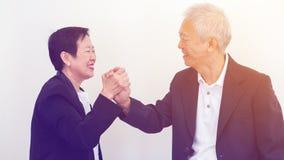 Azjatyccy starsi ludzie biznesu pary mienia ręki dla pomyślnego Fotografia Royalty Free