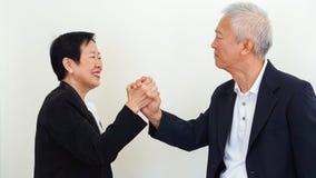 Azjatyccy starsi ludzie biznesu pary mienia ręki dla pomyślnego Fotografia Stock